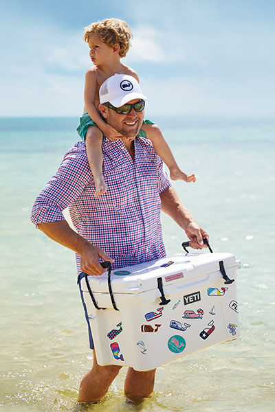 brett ekblom holding a cooler, standing in the water with his son on his shoulders
