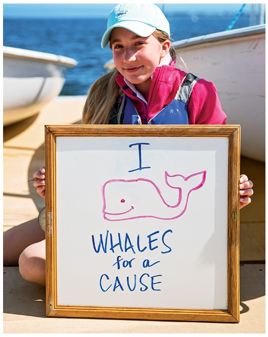 Image of girl holiding a I Whale Whales For A Cause sign.