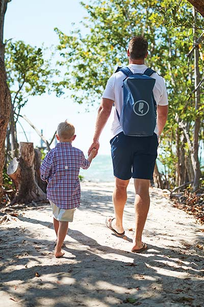 brett ekblom walking to the beach with a vineyard vines backpack, holding his son's hand