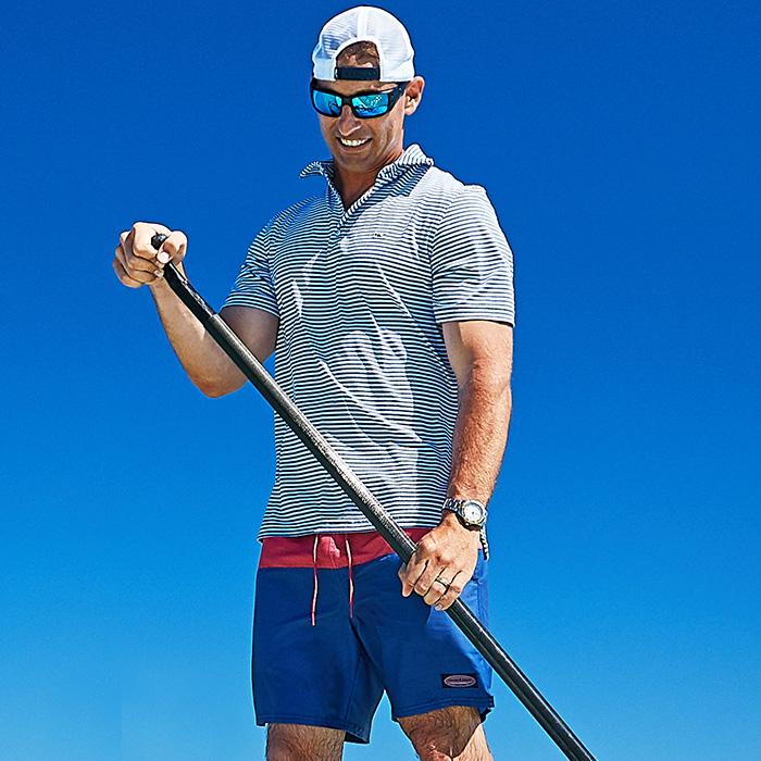 a man in a sankaty polo holding an oar