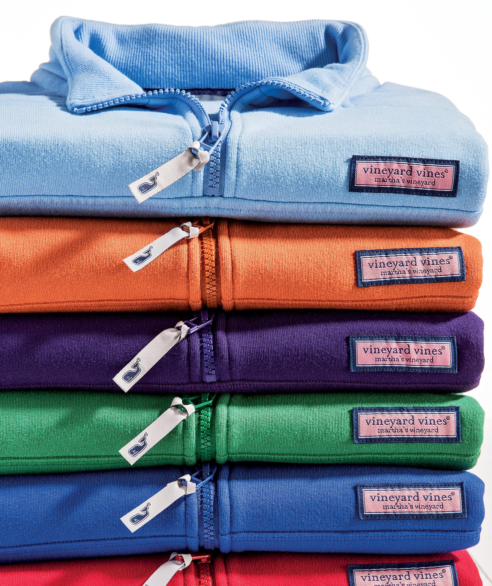 stack of collegiate colored shep shirts