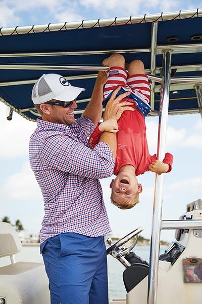 brett ekblom on a boat holding his son upside down