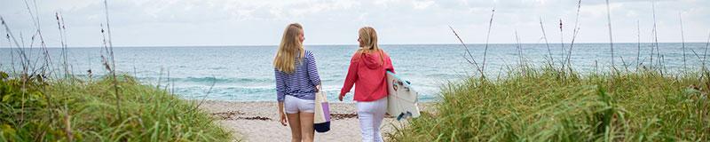 two women walking towards the water