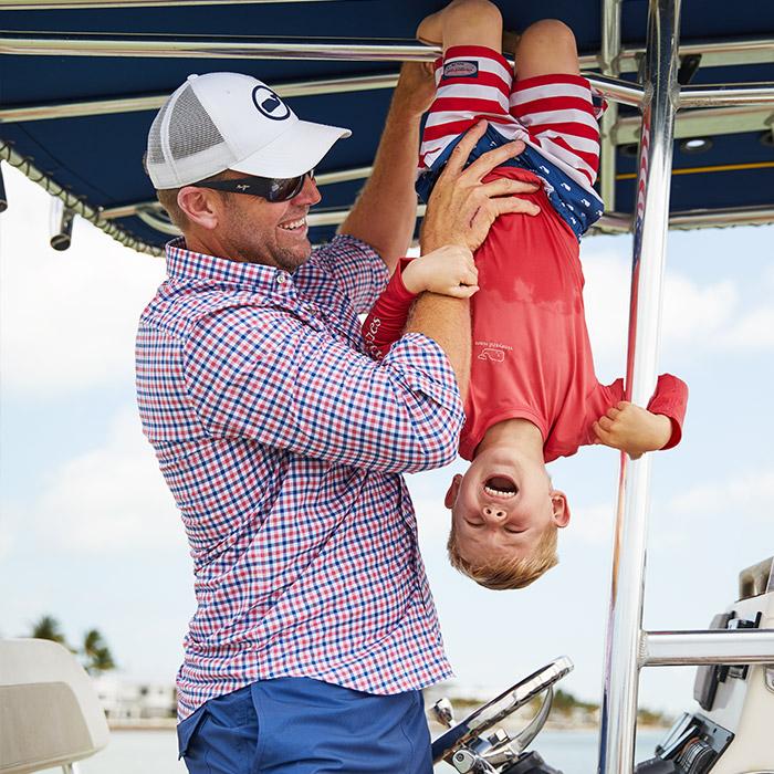 man in performance tucker shirt holding boy upside down on boat