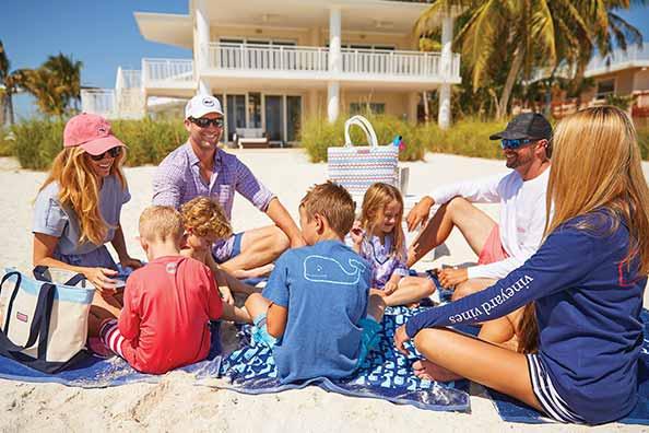 brett ekblom sitting with his family on the beach